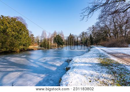 Snow Landscape In Winter, Frozen Lake, Trees Near The Water
