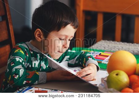 Adorable Little Boy Opens Page Of Exercise Book. Cute Boy Reading Book On Chair At Home. Happy Child