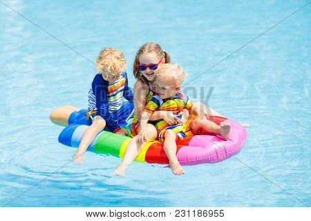 Boy And Girl On Inflatable Ice Cream Float In Outdoor Swimming Pool Of Tropical Resort. Summer Vacat