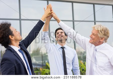 Closeup Of Business Team Of Three Smiling Diverse People High Fiving And Standing Outdoors With Buil