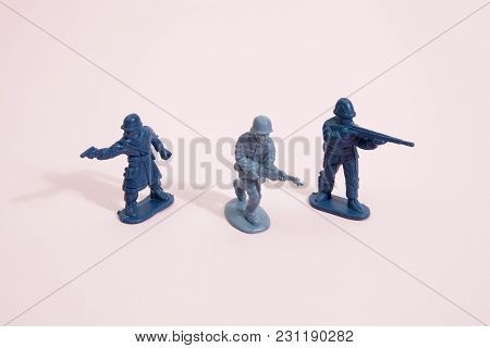 Three Plastic Toy Soldier On A Pop Vibrant Pink Background. Minimal Color Still Life Photography
