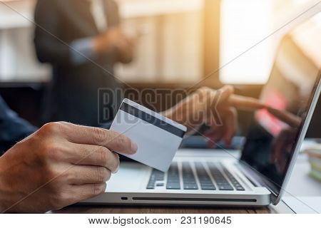 Businessman Holding Credit Card And Using Laptop Computer. Online Shopping Concept