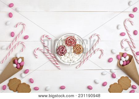 Frame Colorful Candies, Striped Lollipops, Cookies, Marshmallows And Lollipops On Plate Top View Whi