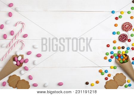Frame Colorful Candies, Marshmallows, Cookies And Striped Lollipops Top View White Wooden Background