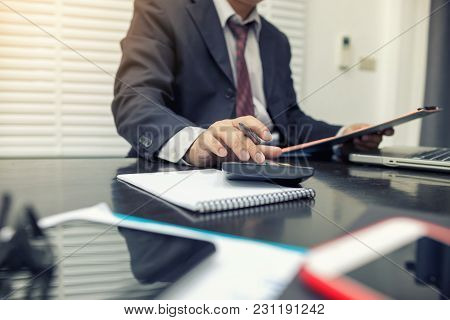 Man Using Calculator And Writing Make Note With Calculate In The Office And Monitoring Financial Inf