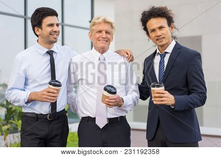 Closeup Of Business Team Of Three Smiling Diverse People Looking At Camera, Holding Drinks In Dispos