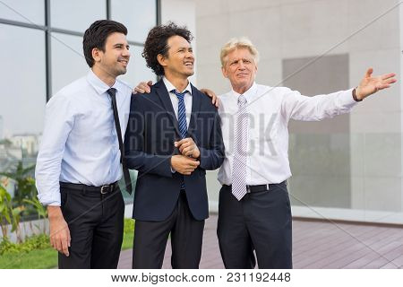 Closeup Of Business Team Of Three Relaxed Diverse People Looking At Something, Talking And Standing