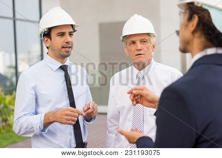 Closeup Of Three Serious Diverse Business People Wearing Helmets, Gesturing, Discussing Issues And S
