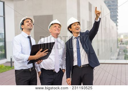 Closeup Of Three Smiling Diverse Business People Wearing Helmets, Looking At Something And Standing