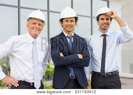 Closeup Portrait Of Three Smiling Diverse Business People Looking At Camera, Wearing Helmets And Sta
