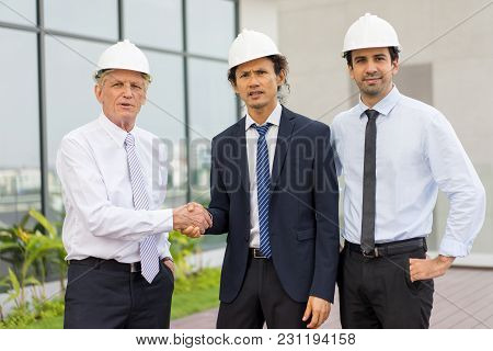 Closeup Portrait Of Three Serious Diverse Business People Looking At Camera, Wearing Helmets, Shakin