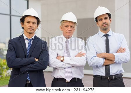 Closeup Of Three Serious Diverse Business People Looking At Camera, Wearing Helmets And Standing Wit