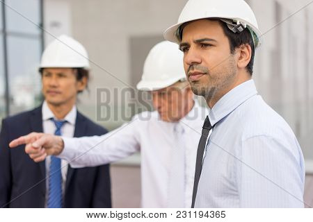 Closeup Portrait Of Three Serious Diverse Business People Looking At Something, Wearing Helmets And