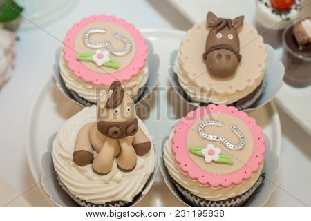 Colorful Cupcakes In A Golden Cases Decorated With Fondant Horse Figures, Hooves, Flowers And Other