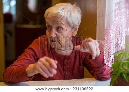 Elderly woman emotional talking and gesturing his hands.