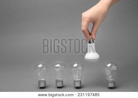 Woman holding LED lamp near incandescent light bulbs on grey background