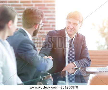 Handshake of colleagues at the desk.