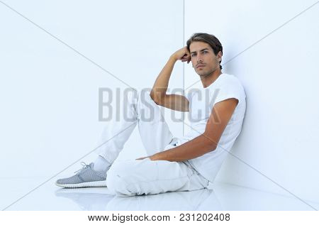 anxious man sitting beside a white wall