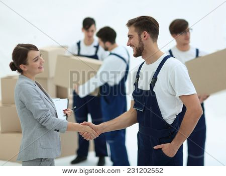 Manager with clipboard shaking hands with movers.