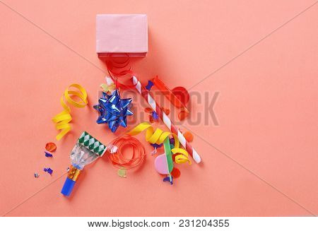 Red Gift Box With Party Confetti, Streamers And Noisemakers On Orange Background. Celebration Concep
