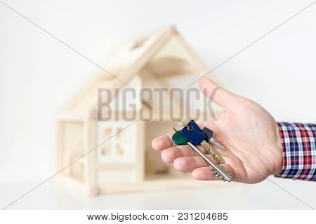 Agent's Hand Hold Keys Against House Model On Background. ..realtor Sale Offer.  Real Estate Investm
