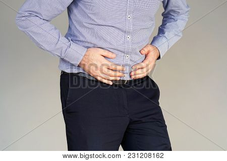 Man Holding His Stomach In Pain On Gray Background. Businessman Suffering From Abdominal Pain. Body