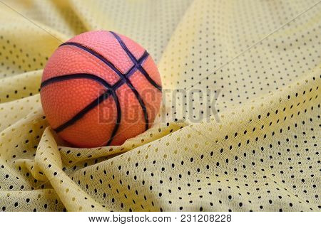 Small Orange Rubber Basketball Lies On A Yellow Sport Jersey Clothing Fabric Texture And Background