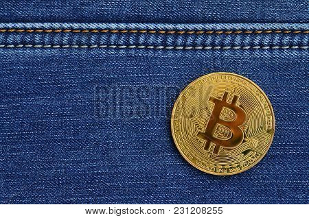 Golden Bitcoin Lies On A Blue Jeans Fabric. New Virtual Money. New Crypto Currency In The Form Of Th
