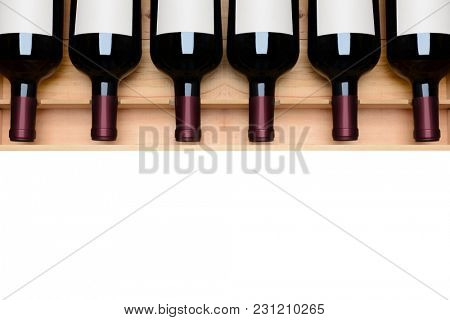 Overhead shot of a case of red wine bottles with blank labels on white with copy space at the bottom. Horizontal format.