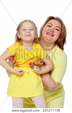 Mom And Little Daughter Plus The Size Of The Model, Gently Embrace. A Woman And Her Daughter Are Smi