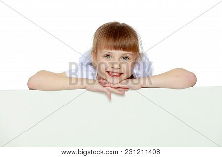Funny Little Blonde Girl With Pigtails And White Bows On Her Head In A White T-shirt And Shorts.she