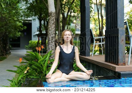 Yoga Woman Sitting In Lotus Position By Swimming Pool On Sunny Day. Concept Of Physical Or Mental Ac