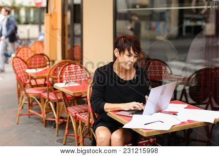 Aged Female Writer Printing In Laptop Have Some Difficulties With Writing New Part Of Novel. Woman D