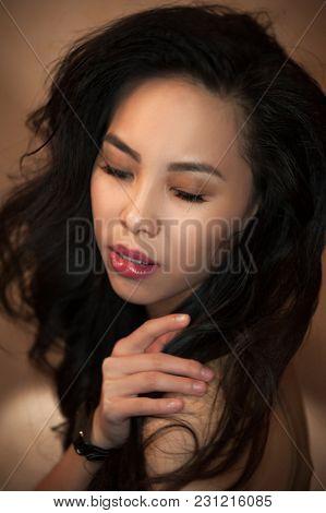 Portrait of beautiful asian girl indoors in warm tones