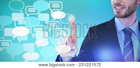 Mid section of smiling businessman touching invisible screen against abstract blue background