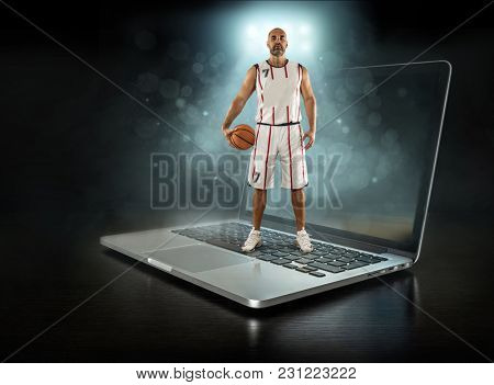 Caucassian Basketball Player stay with ball in a professional sport game play on the laptop.