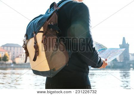 A Young Tourist Man With A Backpack Standing Next To The River Vltava In Prague Looks At The Map And
