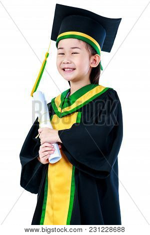 Kindergarten Graduation. Happy Asian Child In Graduation Gown And Cap Holding Diploma Certificate At