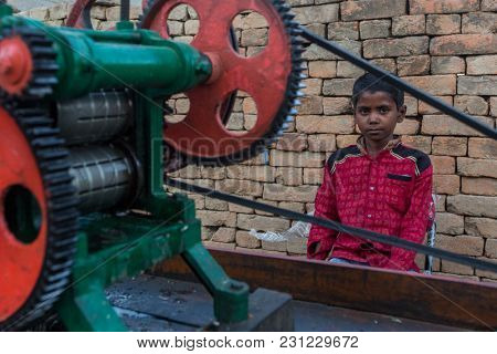 VARANASI, INDIA - MAR 14, 2018: Unidentified indian child seller of cane juice sits near the juicer on the street. According to legends, the city was founded by God Shiva about 5000 years ago.