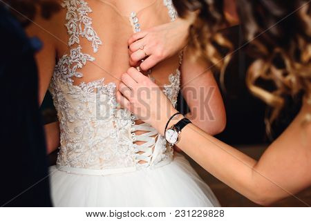 Bridesmaid Hands Fastens Buttons On The Back Of The Bride On The Wedding Dress With Beige Corset Clo