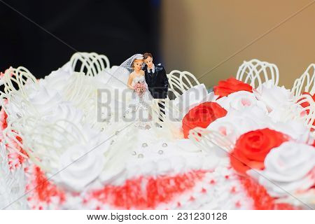 Wedding Cake White Cream Decorated With Red Roses With Figures Of The Bride And Groom Close-up