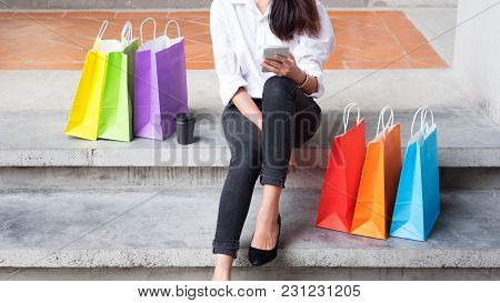 Beautiful Woman Using A Smartphone Standing By A Fashion Store With Shopping Bags.