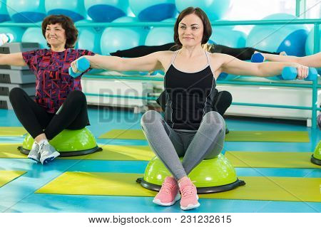 Women Doing Workout Exercise With Dumbbells Sitting On Balance Board In A Gym