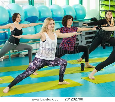 Two Females Doing Yoga Exercise In Sport Gym