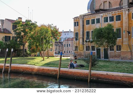 Venice, Italy - August 13, 2016: Tourists Resting In Small Park Near Water