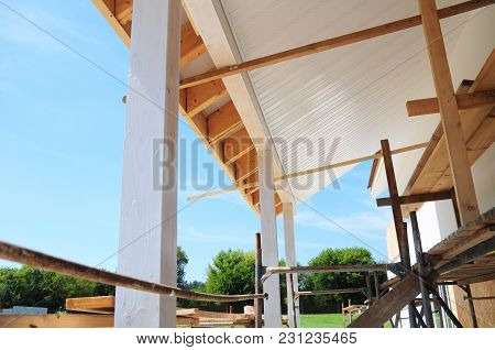 Building House Patio Roofing With Wooden Pillars And Unfinished Soffits And Fascia Boards Installati