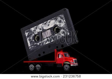 Music Concept Red Truck And Audio Music Tape On A Black Background