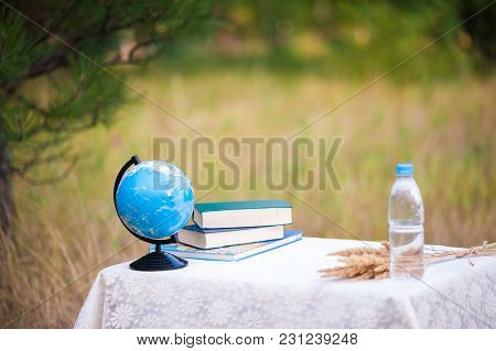 Globe, Books And A Bottle Of Water At A Table In The Background Of Nature. School Desk On The Last O