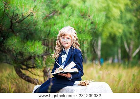 The Girl Is A First Grader Sitting At A Table And Holding An Open Book In Her Hands. A Schoolgirl In