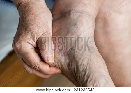 Closeup of elderly hand massaging foot